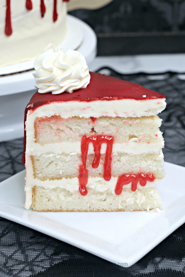 Up-close-picture-of-a-slice-of-iced-vampire-cake-sitting-on-a-white-cake-stand-700x1050